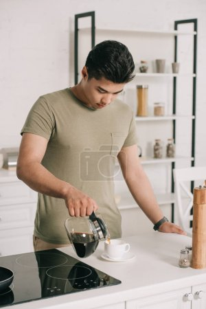 Photo for Handsome asian man pouring coffee in cup from coffee pot in kitchen - Royalty Free Image