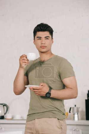 Photo for Pensive asian man drinking coffee while standing in kitchen and looking away - Royalty Free Image