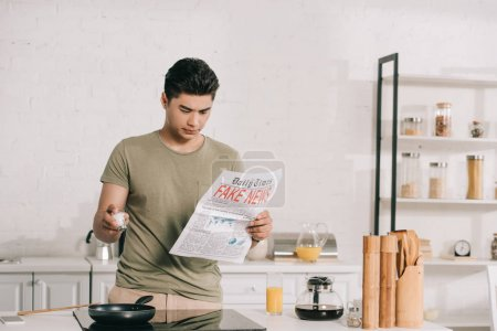 Photo for Handsome asian man preparing breakfast while reading fake news newspaper in kitchen - Royalty Free Image
