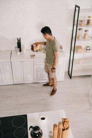 Photo pour Vue d'angle élevé du jeune homme ajoutant des flocons dans le bol tout en restant près de la table de cuisine - image libre de droit