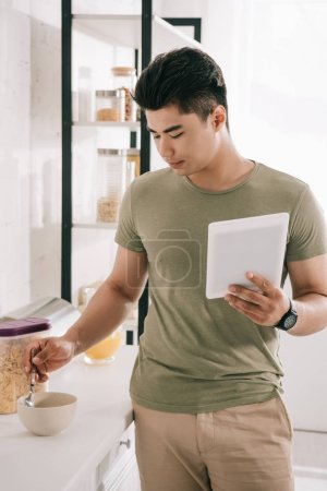 Photo pour Bel homme asiatique mélange flocons dans bol tout en tenant tablette numérique dans la cuisine - image libre de droit