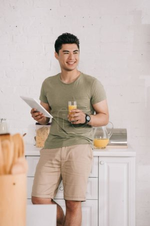 Photo for Handsome asian man holding glass with orange juice and digital tablet while smiling and looking away in kitchen - Royalty Free Image