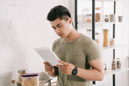 Photo pour Concentré asiatique l'homme en utilisant numérique tablette tandis que debout près de cuisine table - image libre de droit