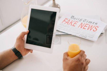 Photo pour Vue recadrée de l'homme tenant verre de jus d'orange et tablette numérique avec écran blanc tout en étant assis à la table de la cuisine près de journal de fausses nouvelles - image libre de droit