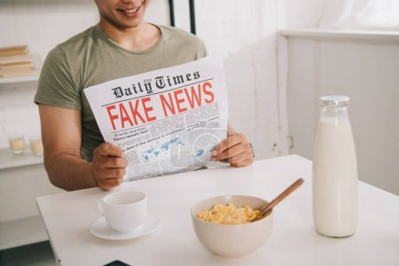 Photo for Cropped view of asian man reading fake news newspaper while sitting at kitchen table near cup of coffee and bowl with flakes - Royalty Free Image