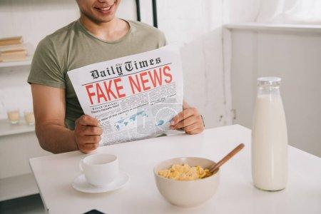 Photo pour Vue recadrée de l'homme asiatique lisant le journal de fausses nouvelles tout en s'asseyant à la table de cuisine près de tasse de café et de cuvette avec des flocons - image libre de droit
