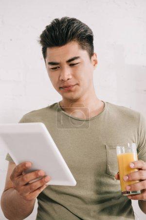 Photo pour Beau homme asiatique lisant le journal de fausses nouvelles tout en retenant le verre du jus d'orange - image libre de droit