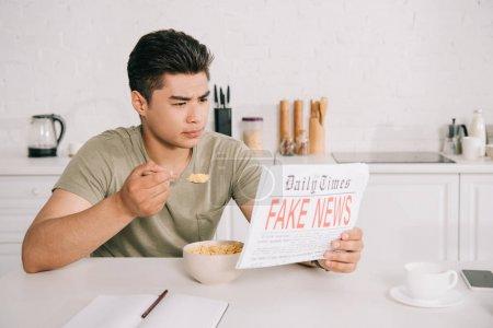 schöner asiatischer Mann frühstückt, während er Fake News Zeitung in der Küche liest