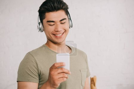 Photo for Cheerful asian man listening music in headphones while looking at smartphone - Royalty Free Image