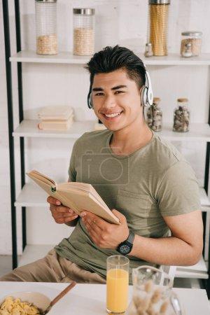Photo pour Gai asiatique homme dans casque souriant à caméra tandis que assis à cuisine table et tenant livre - image libre de droit
