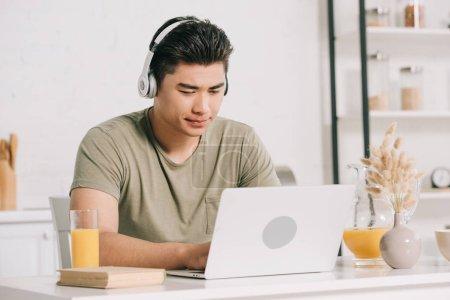 Photo pour Homme asiatique concentré dans l'écouteur utilisant l'ordinateur portatif tout en s'asseyant à la table de cuisine - image libre de droit
