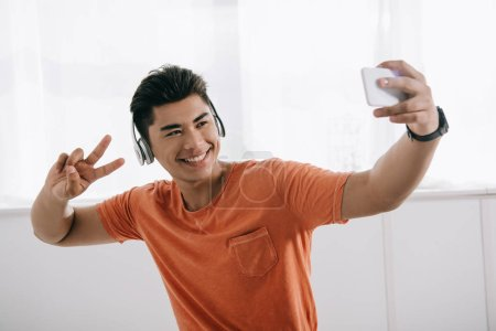 Photo for Happy asian man taking selfie while showing victory gesture and listening music in headphones - Royalty Free Image