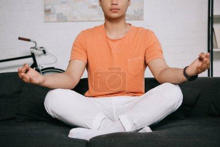 Photo pour Vue recadrée de jeune homme méditant tout en s'asseyant sur le sofa dans la pose de lotus - image libre de droit