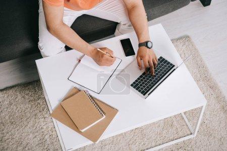 Photo pour Vue recadrée de jeune homme utilisant l'ordinateur portatif et écrivant dans le cahier tout en s'asseyant sur le sofa près du bureau - image libre de droit