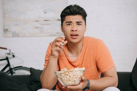 Photo pour Homme asiatique choqué manger du pop-corn et regarder la télévision tout en s'asseyant sur le canapé à la maison - image libre de droit