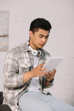 Photo pour Homme asiatique réfléchi utilisant tablette numérique tout en étant assis dans le canapé à la maison - image libre de droit