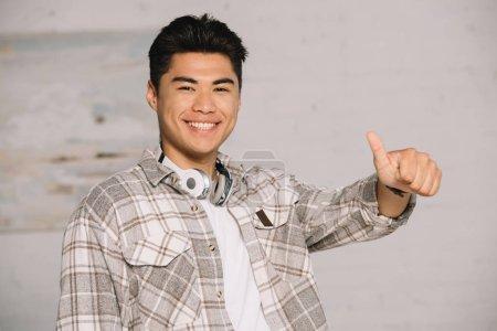 Photo for Cheerful asian man showing thumb up while smiling at camera at home - Royalty Free Image
