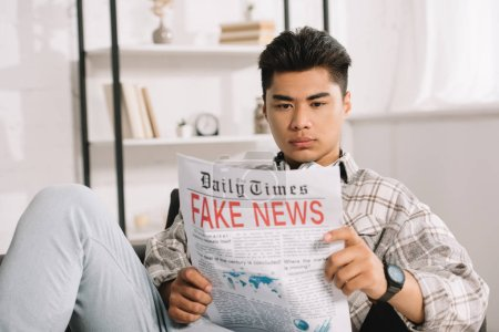 Photo for Serious asian man sitting in sofa at home and reading fake news newspaper - Royalty Free Image