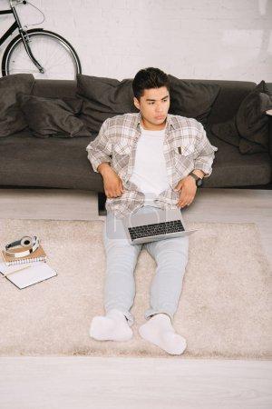 Photo pour Vue aérienne de l'homme asiatique pensif s'asseyant sur l'étage avec l'ordinateur portatif et regardant loin - image libre de droit