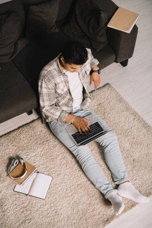 Photo pour Vue aérienne du jeune homme s'asseyant sur l'étage près du divan et utilisant l'ordinateur portatif à la maison - image libre de droit