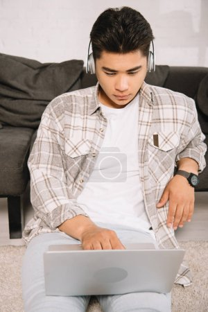 attentive asian man in headphone using laptop while sitting on floor at home