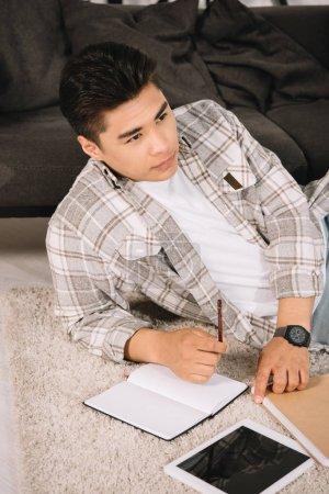 Photo pour Cher asiatique homme regardant loin tandis que couché sur le sol près de portable et tablette numérique avec écran blanc - image libre de droit
