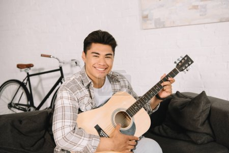 Photo for Cheerful asian man playing acoustic guitar while smiling at camera - Royalty Free Image