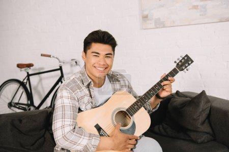 Photo pour Homme asiatique gai jouant la guitare acoustique tout en souriant à l'appareil-photo - image libre de droit