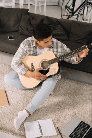 Photo for Young asian man sitting on sofa at home and playing acoustic guitar - Royalty Free Image