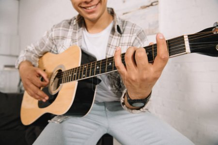 Photo for Partial view of smiling young man playing acoustic guitar at home - Royalty Free Image