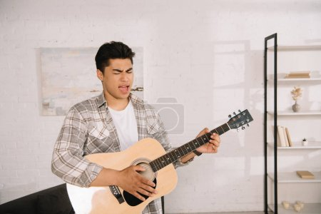 Photo for Handsome asian man playing acoustic guitar and singing at home - Royalty Free Image