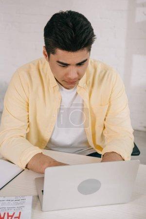 Photo pour Homme asiatique attentif s'asseyant au bureau et utilisant l'ordinateur portatif à la maison - image libre de droit