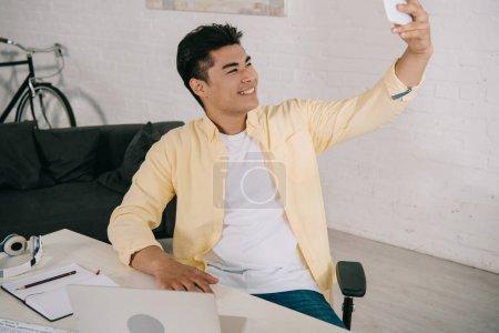 Photo pour Homme asiatique souriant prenant le selfie avec le smartphone tout en s'asseyant au bureau à la maison - image libre de droit