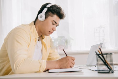 Photo for Young, concentrated asian man in headphones writing in notebook white sitting at desk - Royalty Free Image