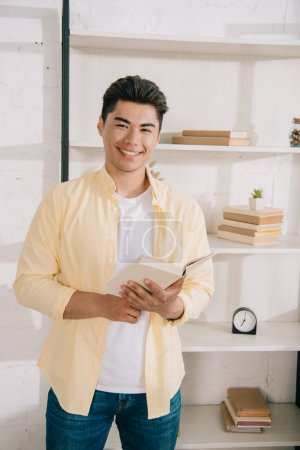 Photo for Young, cheerful asian man holding book while standing near rack and smiling at camera - Royalty Free Image