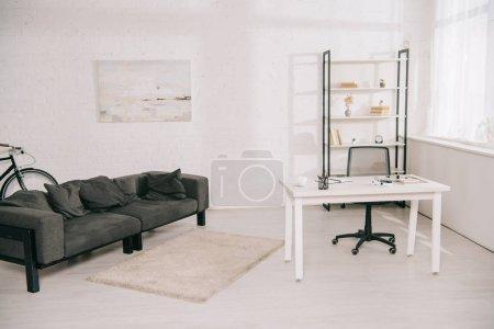 Photo pour Salon spacieux avec canapé gris, table blanche et rack avec livres - image libre de droit