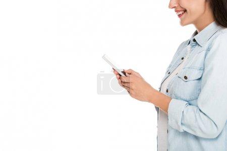 Photo pour Vue latérale d'une jeune femme souriante utilisant un smartphone isolé sur blanc - image libre de droit