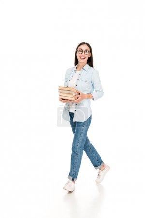 Photo pour Fille heureuse de brunette dans des glaces dans la veste de denim marchant avec des livres d'isolement sur le blanc - image libre de droit
