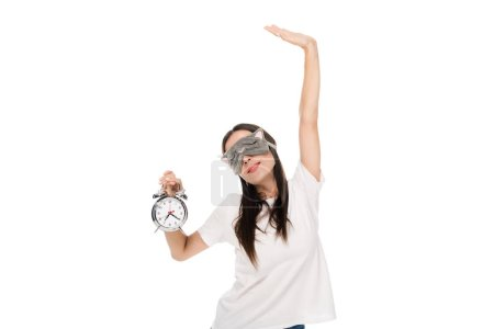 Photo for Brunette young woman in cat sleeping eye mask outstretching herself and holding alarm clock isolated on white - Royalty Free Image