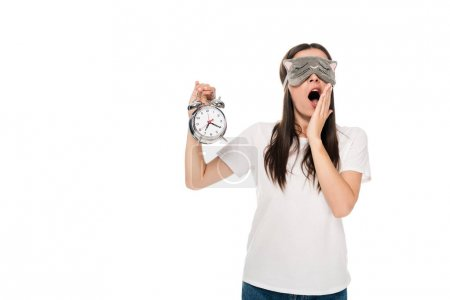 Photo for Brunette young woman in cat sleeping eye mask yawning and holding alarm clock isolated on white - Royalty Free Image