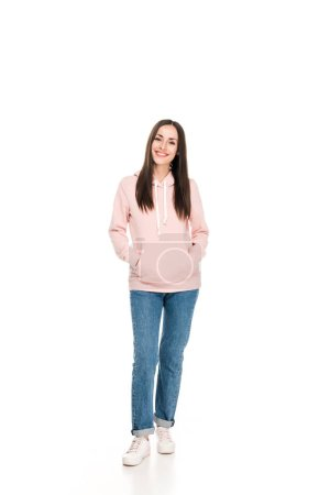 Photo for Full length view of smiling girl in casual outfit standing with hands in pockets isolated on white - Royalty Free Image