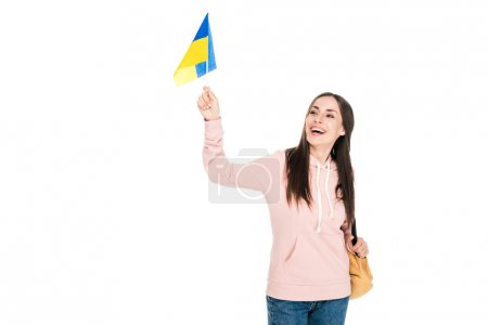 Photo pour Fille de brunette de sourire avec le sac à dos retenant le drapeau ukrainien d'isolement sur le blanc - image libre de droit