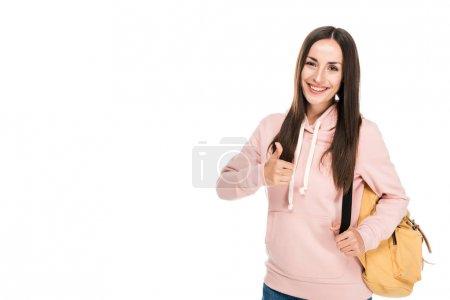 Photo pour Fille brune souriante avec sac à dos montrant pouce vers le haut isolé sur blanc - image libre de droit