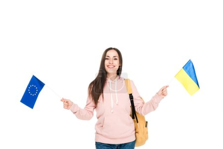 smiling student with backpack holding Ukrainian and European flags isolated on white