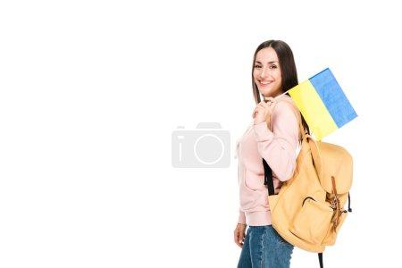 Photo pour Vue de côté de l'étudiant de sourire avec le sac à dos retenant le drapeau ukrainien d'isolement sur le blanc - image libre de droit