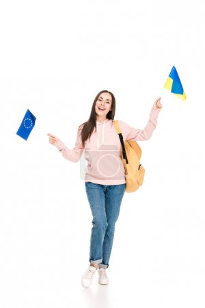 full length view of smiling student with backpack holding Ukrainian and European flags isolated on white