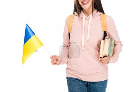 Photo pour Vue recadrée de l'étudiant de sourire avec le sac à dos retenant le drapeau ukrainien et les livres d'isolement sur le blanc - image libre de droit