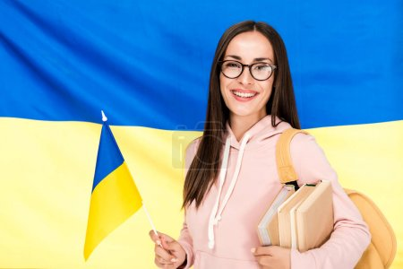 Photo pour Smiling brunette young woman in glasses with backpack, flag and books on Ukrainian flag background - image libre de droit