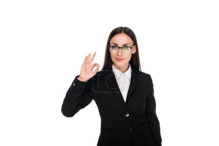 Photo pour Femme d'affaires de sourire dans le procès noir affichant le signe ok d'isolement sur le blanc - image libre de droit