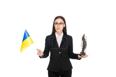 Photo pour Lawyer in suit holding Ukrainian flag and bronze Themis statuette isolated on white - image libre de droit